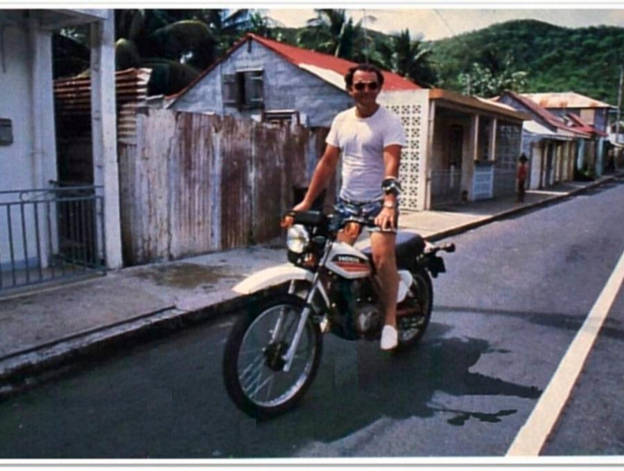 Coluche faisant de la moto en Guadeloupe